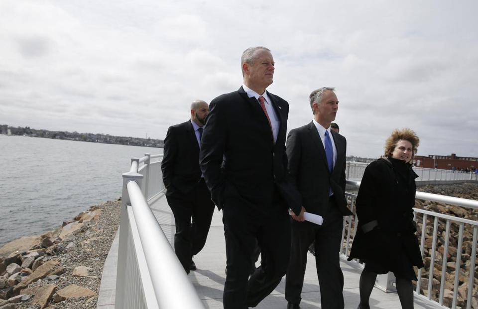 New Bedford, Massachusetts -- 4/19/2017 - (L-R) Governor Baker, New Bedford Mayor Jon Mitchell and Transportation Secretary Stephanie Pollack walk down the CoveWalk as part of a photo op at the opening of the CoveWalk, the city's newest recreational waterfront path. The 5,500 foot path rests on top of the city's Hurricane Barrier. (Jessica Rinaldi/Globe Staff) Topic: Reporter: